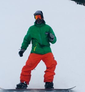der Männeryoga Lehrer beim Snowboarden